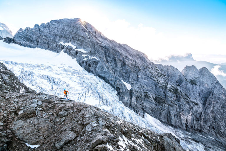 A trail runner on the Dossen Peak, with the Rosenlauigletscher in the background, Swiss Alps