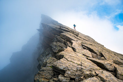 A trail runner running up a steep rocky ridge line, above Saas Almagell, Switzerland