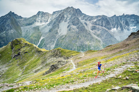 Trail running in a wide open flower covered rocky landscape above Arolla, Switzerland