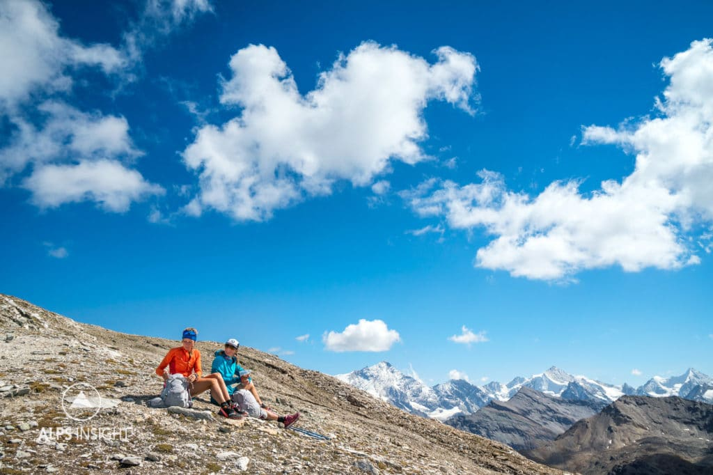 Runners stopped to sit and enjoy the landscape of the Swiss Alps while running the Via Valais, a multi-day trail running tour connecting Verbier with Zermatt, Switzerland.