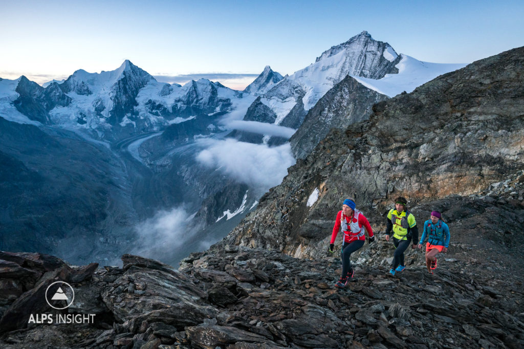 Runners hiking up the Pigne de la Lé, 3396 meter, at sunrise during the Via Valais, a multi-day trail running tour connecting Verbier with Zermatt, Switzerland.