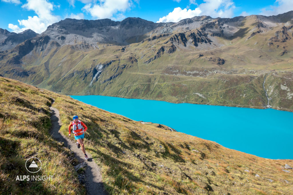 Trail running above Lac de Moiry's turquoise water during the Via Valais, a multi-day trail running tour connecting Verbier with Zermatt, Switzerland.