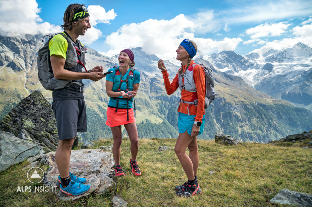 A group of runners stand eating wild blueberries while they look at the navigation app on their phone, during the Via Valais, a multi-day trail running tour connecting Verbier with Zermatt, Switzerland.
