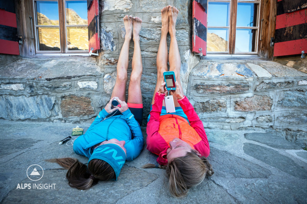Two women lay on the ground outside the Turtmann Hut looking at the phone, and charging the watch with legs up, relaxing after trail running during the Via Valais, a multi-day trail running tour connecting Verbier with Zermatt, Switzerland.
