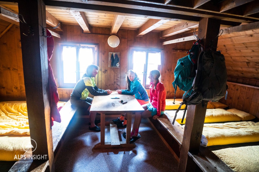 Friends sit around in a sleeping room of the Turtmann Hut during the Via Valais, a multi-day trail running tour connecting Verbier with Zermatt, Switzerland.