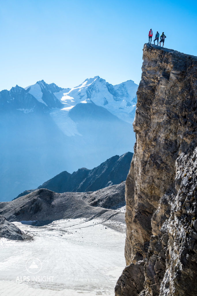 Runners standing on the top of a peak near the Barrhorn, while running the Via Valais, a multi-day trail running tour connecting Verbier with Zermatt, Switzerland.