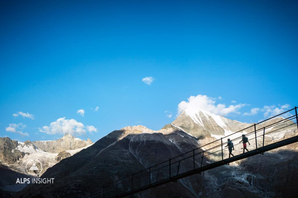 Runners crossing the world's longest suspension bridge, the Europaweg Bridge, while on the Via Valais, a multi-day trail running tour connecting Verbier with Zermatt, Switzerland.